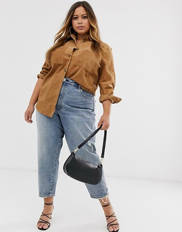 A plus-size model wearing a corduroy button-up top.
