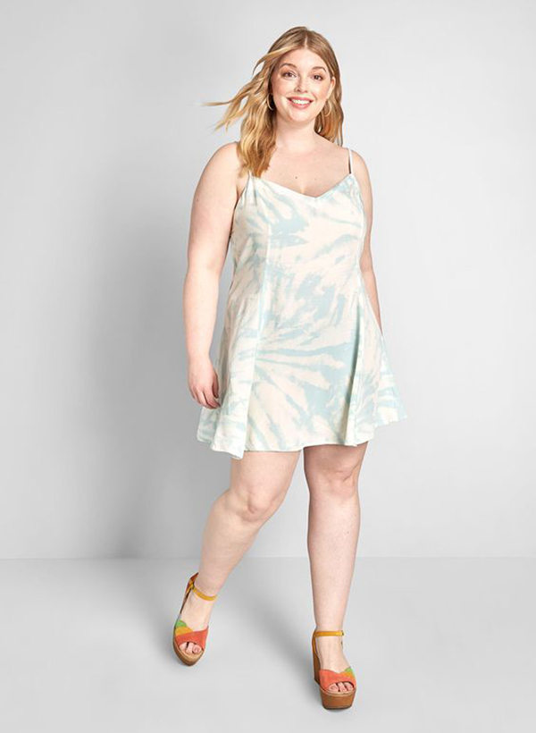 A model wearing a light blue tie-dye plus-size dress.