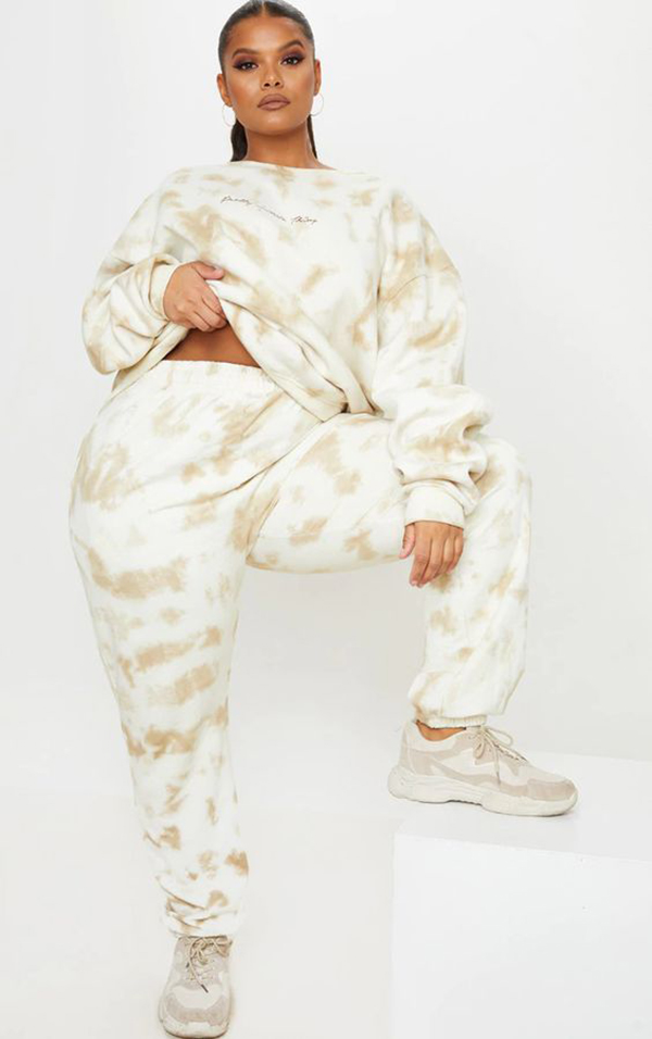 A model wearing a tan and white plus-size loungewear set.