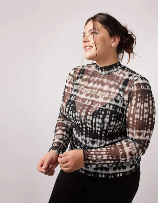 A model wearing a black and white tie-dye plus-size top.