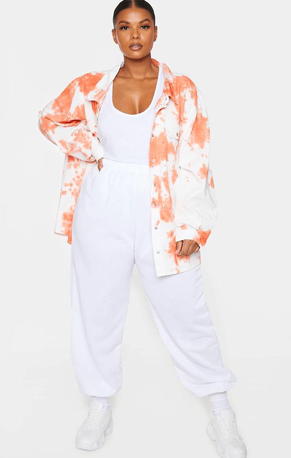 A plus-size model wearing an orange tie-dye jacket.