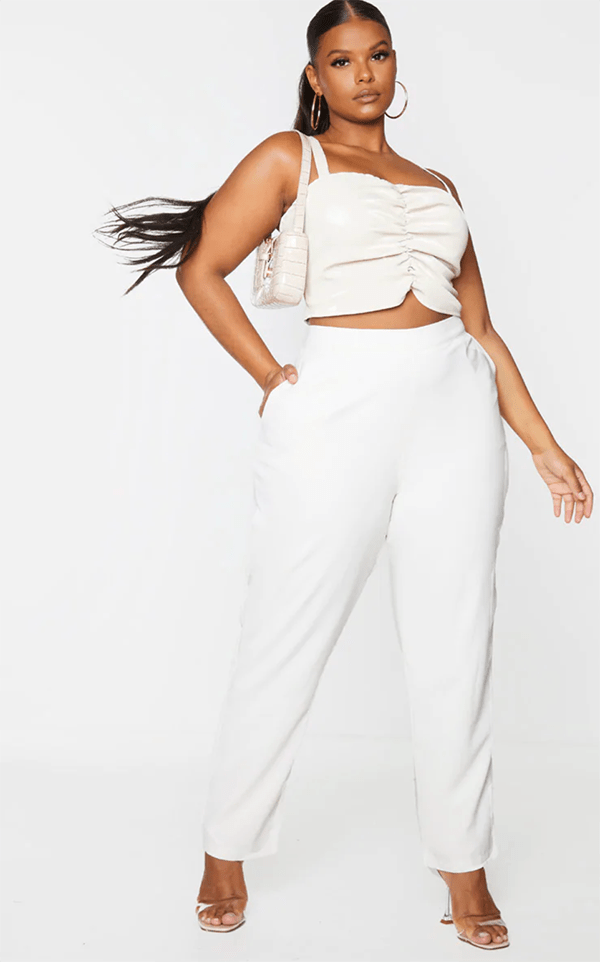 A plus-size model wearing a white ruched crop top.