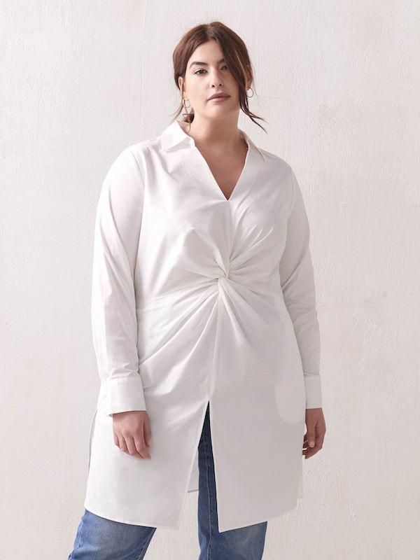 A woman wearing a twist front white blouse.