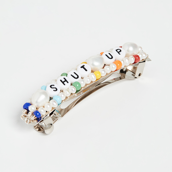 A hair barrette covered in pearls, seed beads, and letter beads.