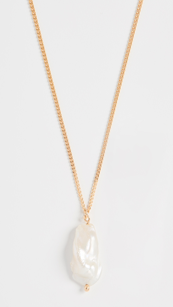A pearl pendant necklace on a gold chain.