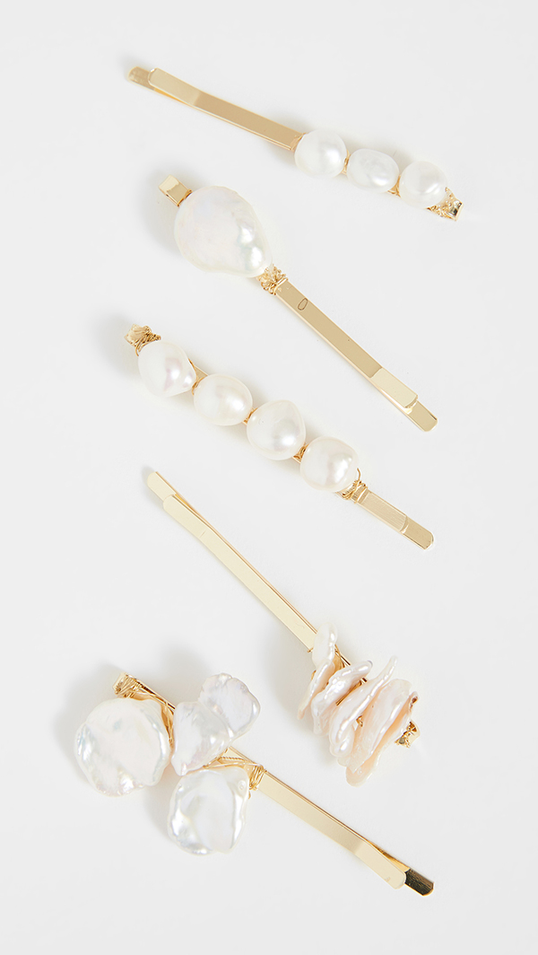 An array of gold bobby pins covered in white shells and pearls.