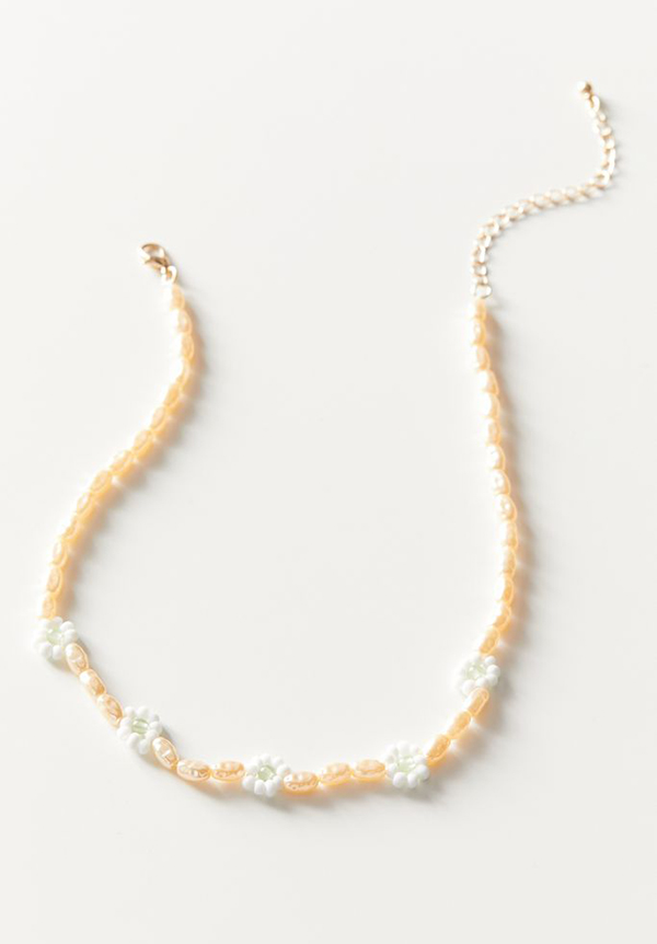 A dainty necklace covered in small pink pearls and small flower-shaped beads.