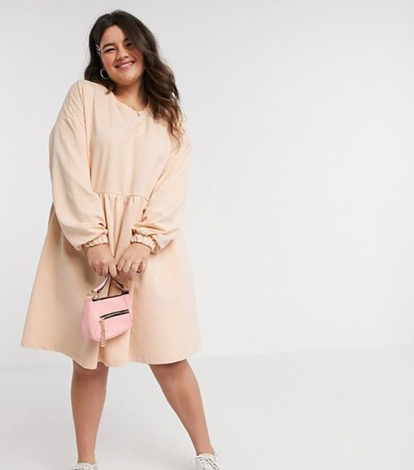 A plus-size model wearing a babydoll sweatshirt dress.