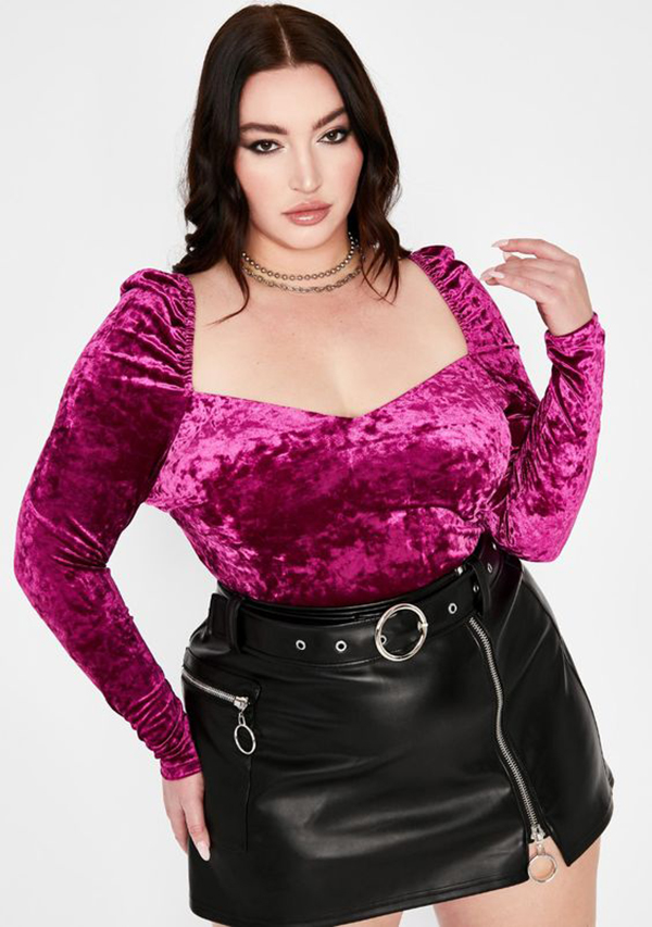A plus-size model wearing a pink velvet bustier top.