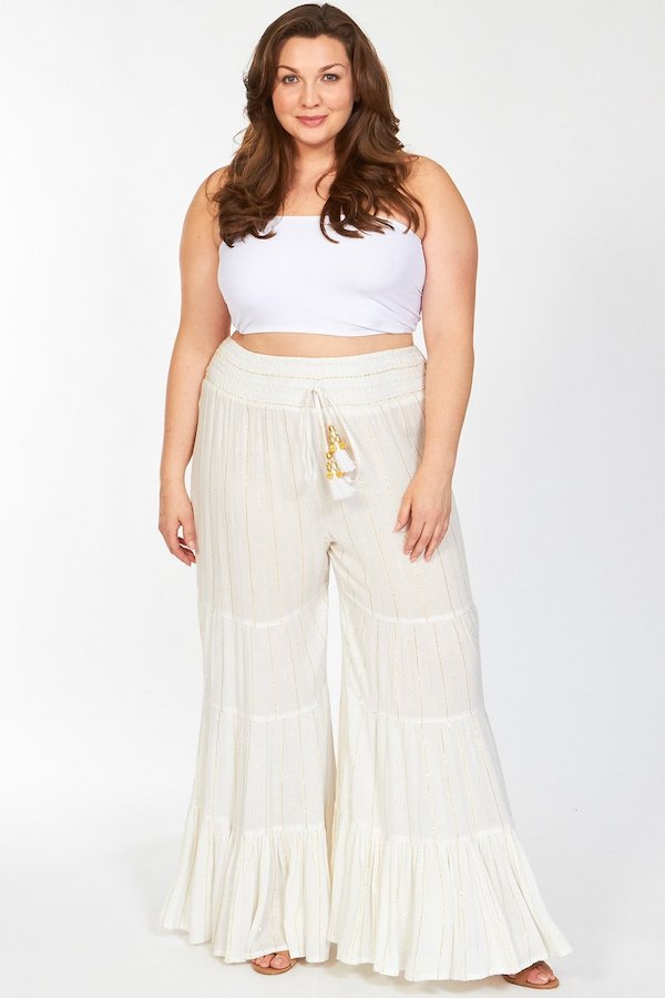 A woman wearing a white top and white tiered flare pants.