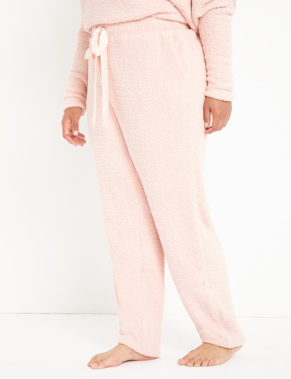 A woman wearing light pink fuzzy pants.