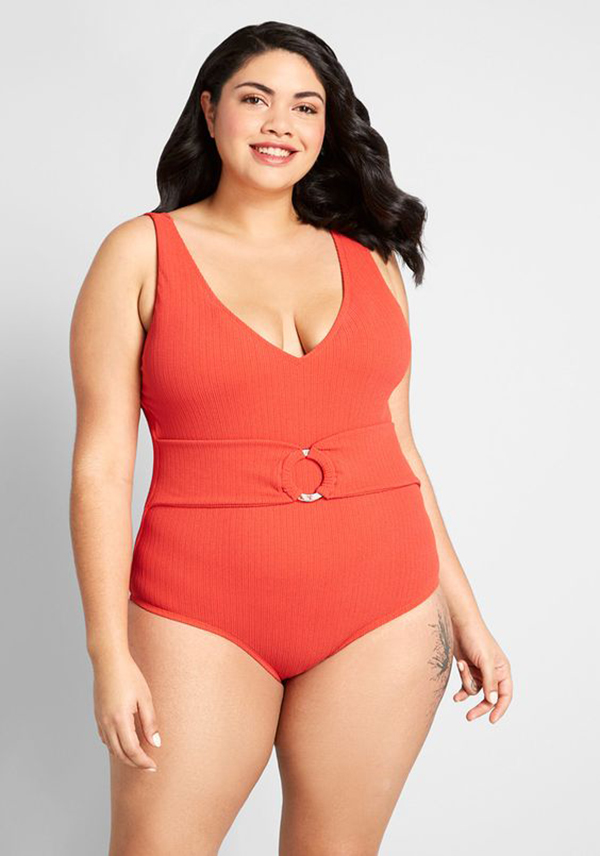 A plus-size model wearing a red-orange belted one-piece swimsuit.