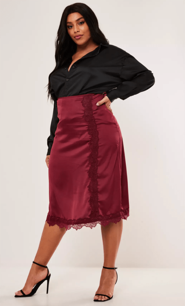 A plus-size model wearing a burgundy, lace-lined satin slip skirt.