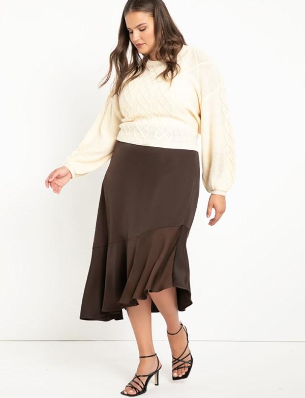 A plus-size model wearing a brown, ruffled satin slip skirt.