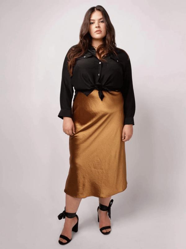 A plus-size model wearing a gold satin slip skirt.