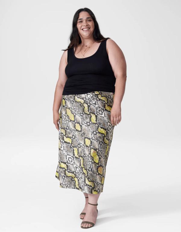 A plus-size model wearing a snake print satin slip skirt.