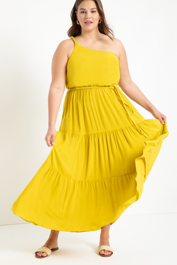 A plus-size model wearing a yellow one-shoulder maxi dress.