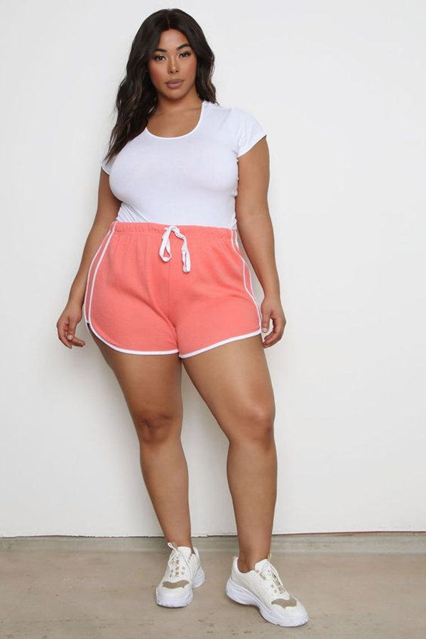 A plus-size model wearing coral sweat shorts.