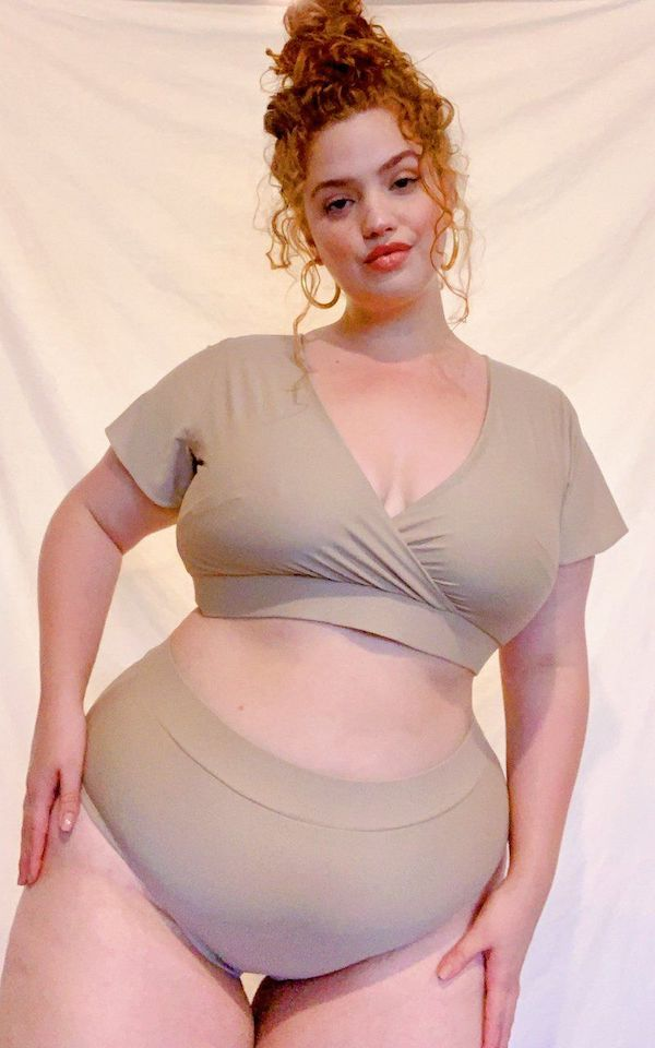 A model wearing a plus-size swimsuit with sleeves in tan.