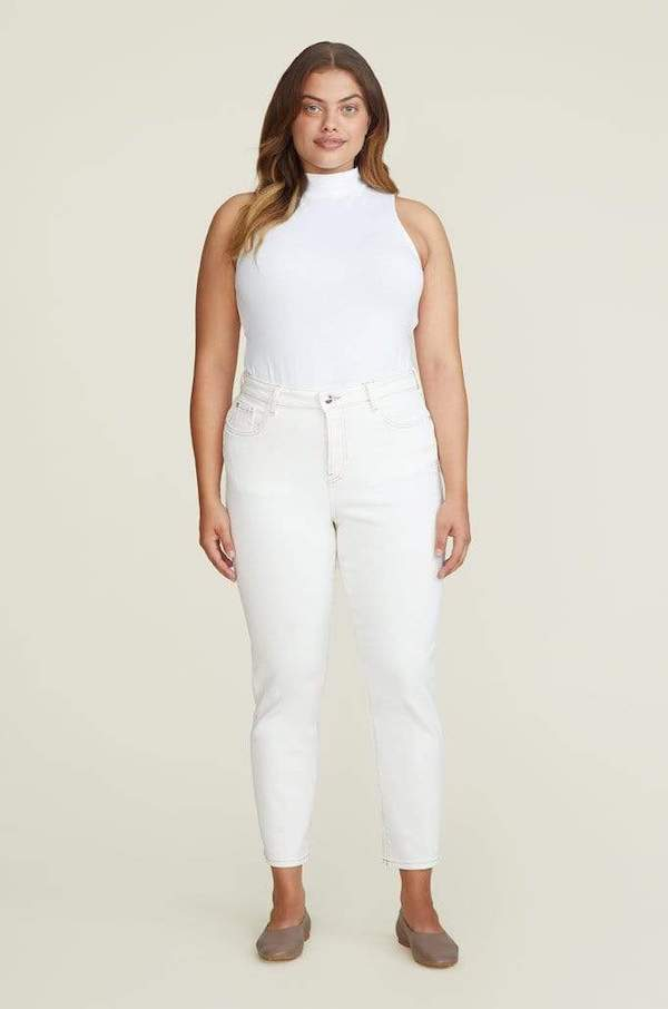 A woman wearing a white tank top and white jeans.