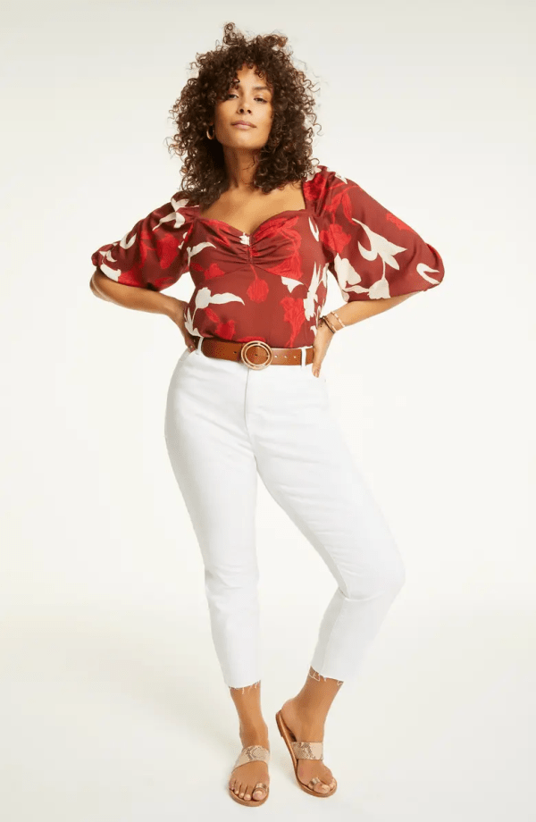 A woman wearing a red floral shirt with white jeans.