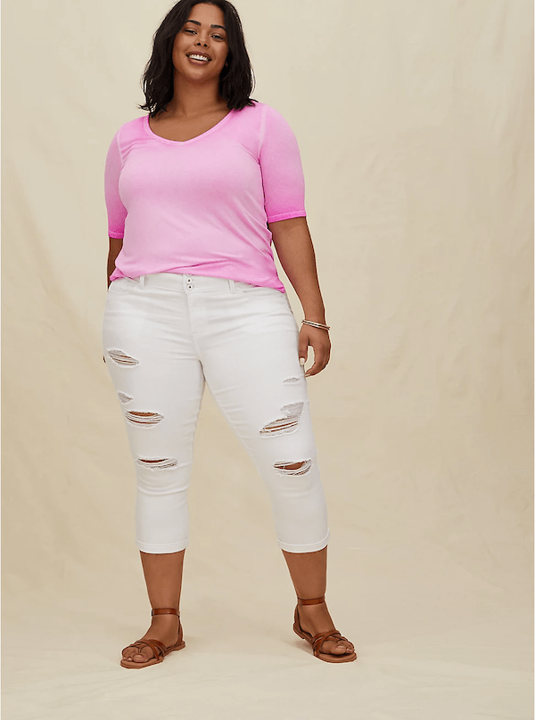 A woman wearing a pink top and white jeans.