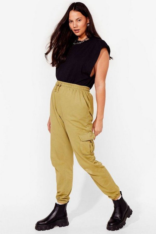 A model wearing a pair of plus-size cargo pants in green.