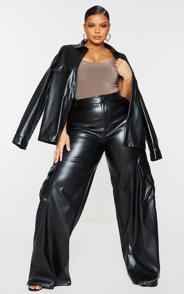 A model wearing a pair of plus-size cargo pants in black.