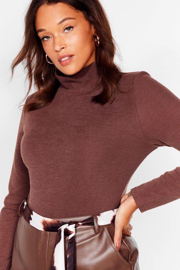 A woman wearing a brown turtleneck bodysuit.