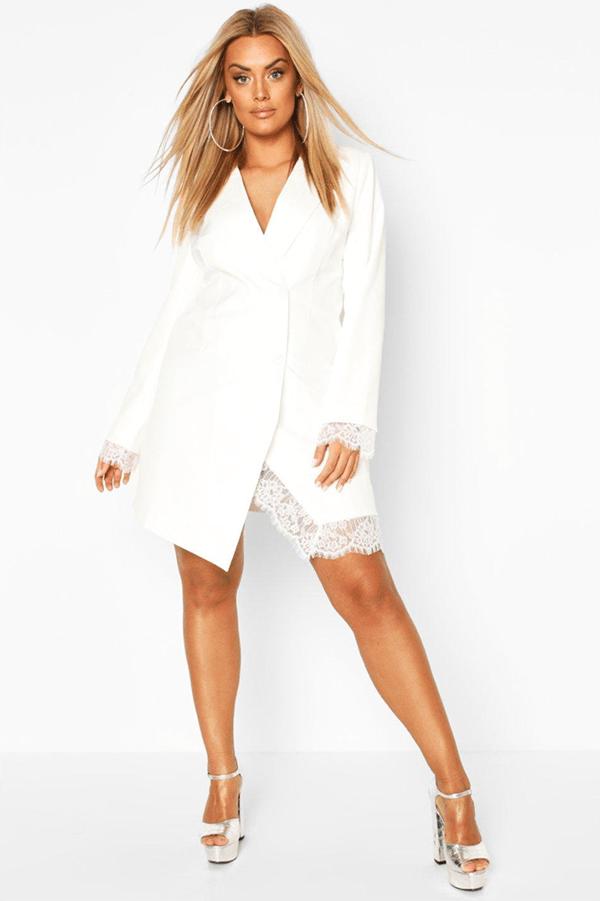 A plus-size model wearing a white blazer dress.