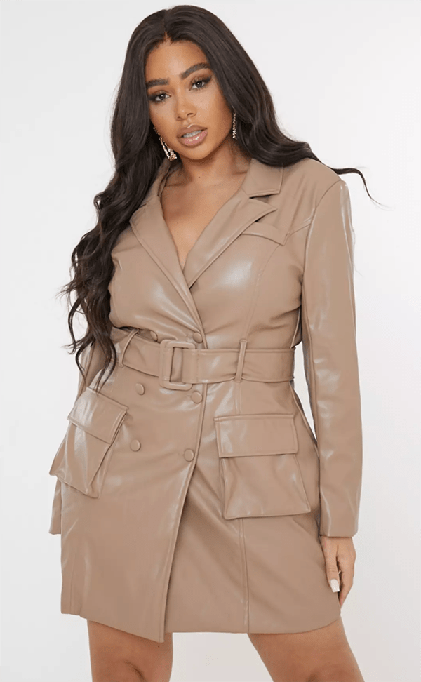 A plus-size model wearing a taupe leather blazer dress.