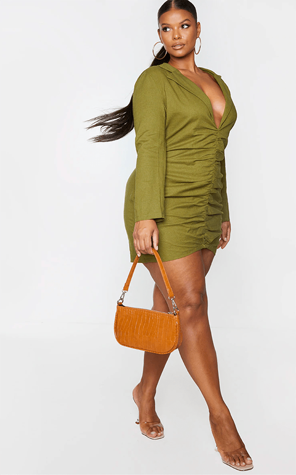 A plus-size model wearing a ruched olive green blazer dress.