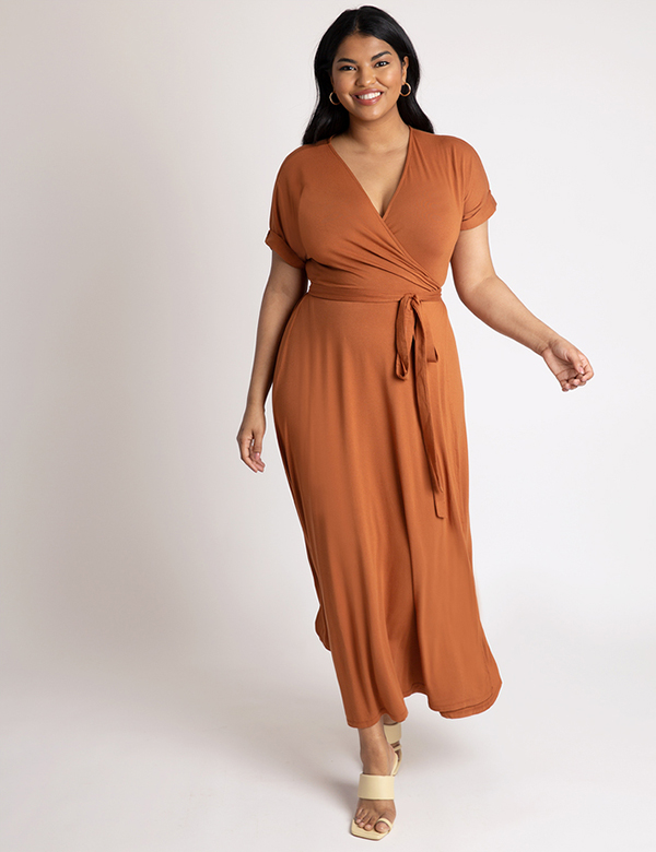 A plus-size model wearing a rust wrap dress, which is now on sale at Eloquii for less than $39.