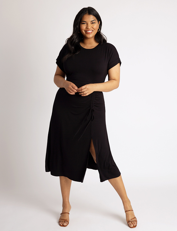 A plus-size model wearing a black ruched dress, which is now on sale at Eloquii for less than $39.