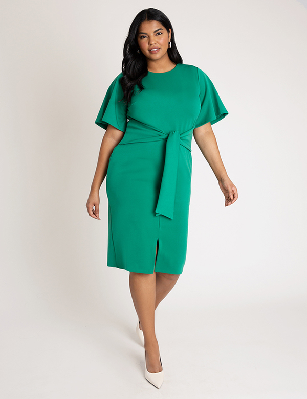 A plus-size model wearing an emerald green cocktail dress, which is now on sale at Eloquii for less than $39.