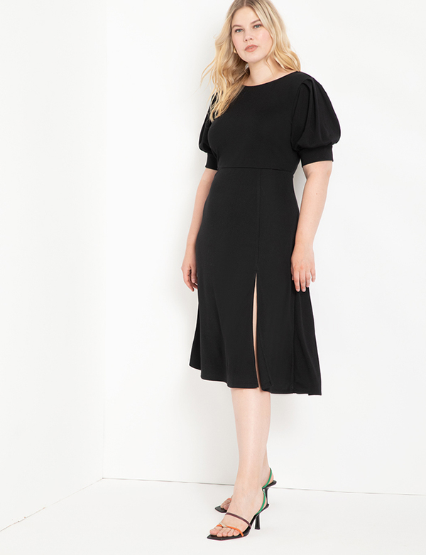 A plus-size model wearing a black puff-sleeve dress, which is now on sale at Eloquii for less than $39.