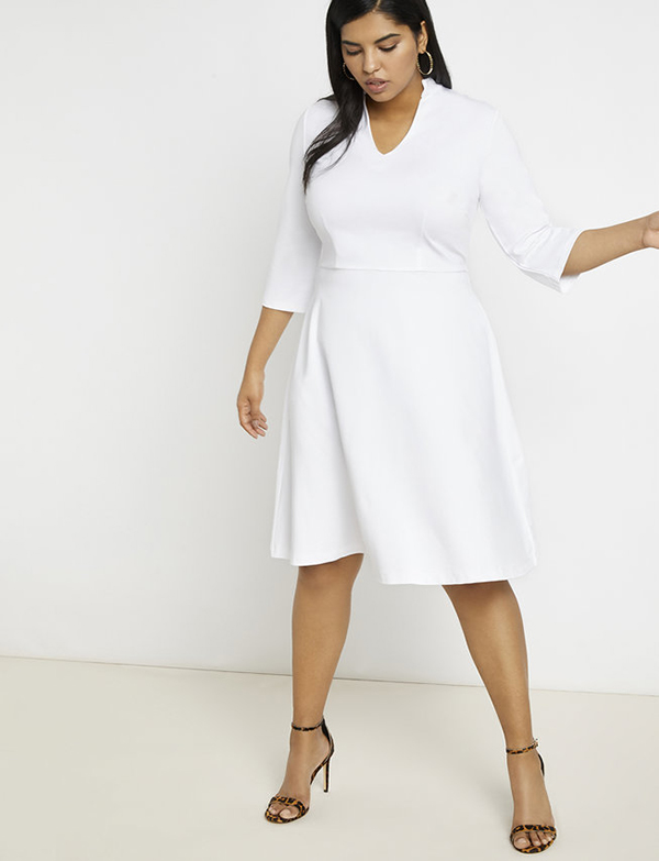 A plus-size model wearing a white cocktail dress, which is now on sale at Eloquii for less than $39.