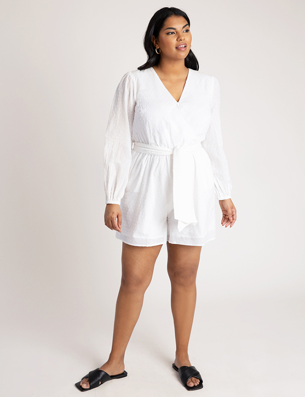A plus-size model wearing a white romper, which is now on sale at Eloquii for less than $39.