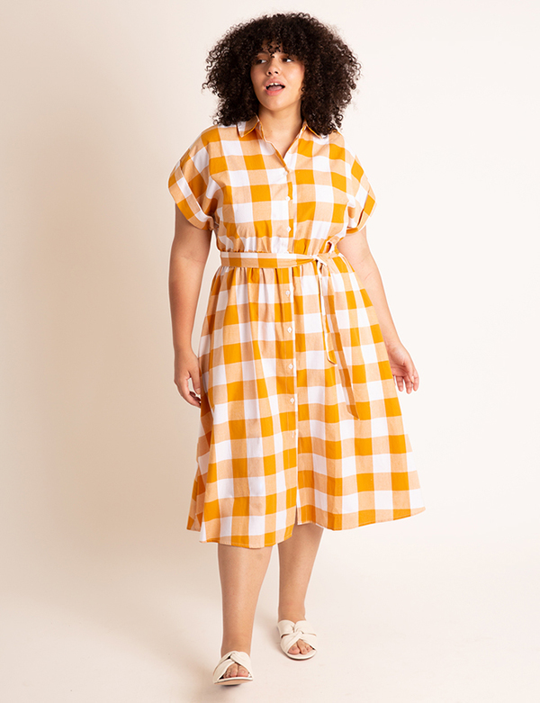 A plus-size model wearing a yellow gingham dress, which is now on sale at Eloquii for less than $49.