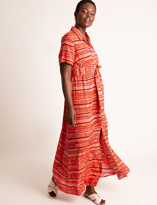 A plus-size model wearing a red printed maxi dress, which is now on sale at Eloquii for less than $49.