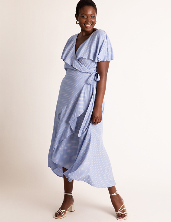 A plus-size model wearing a periwinkle ruffled dress, which is now on sale at Eloquii for less than $49.