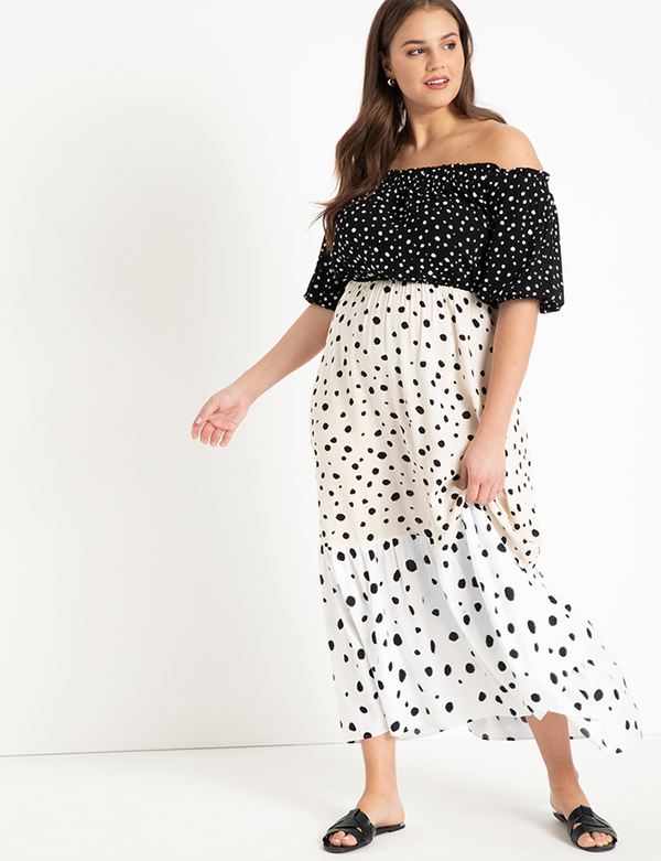 A plus-size model wearing a polka dot maxi dress, which is now on sale at Eloquii for less than $49.