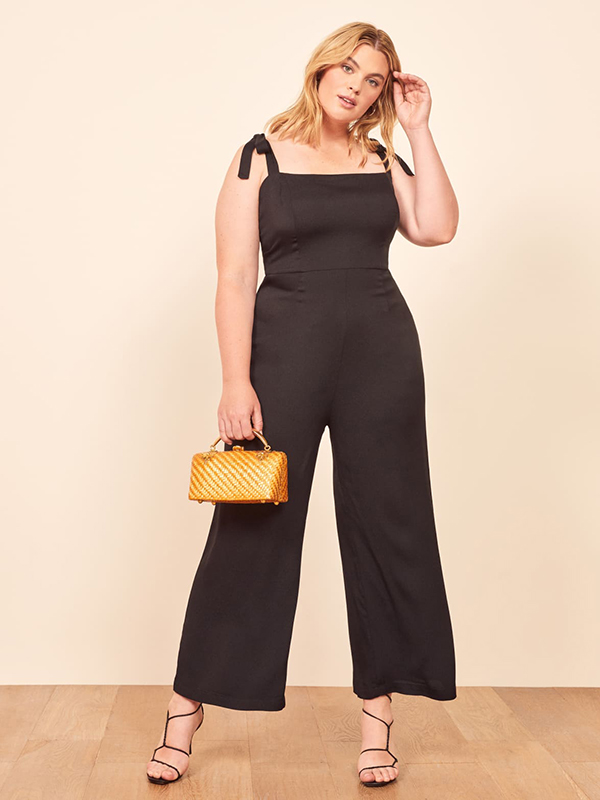 A plus-size model wearing a black jumpsuit, which are currently on sale at Reformation.