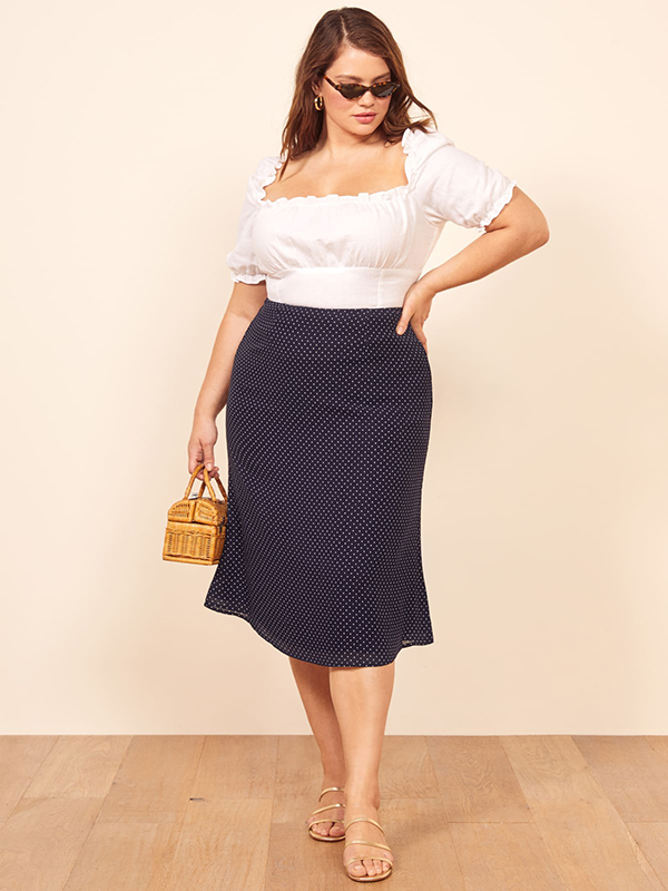 A plus-size model wearing a navy midi skirt, which is currently on sale at Reformation.