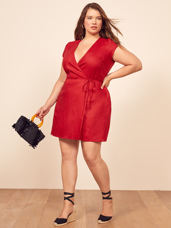 A plus-size model wearing a red mini dress, which is currently on sale at Reformation.