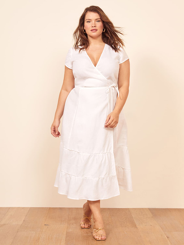 A plus-size model wearing a white wrap midi dress, which are currently on sale at Reformation.