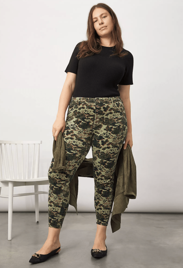 A plus-size model wearing green printed corduroy pants.