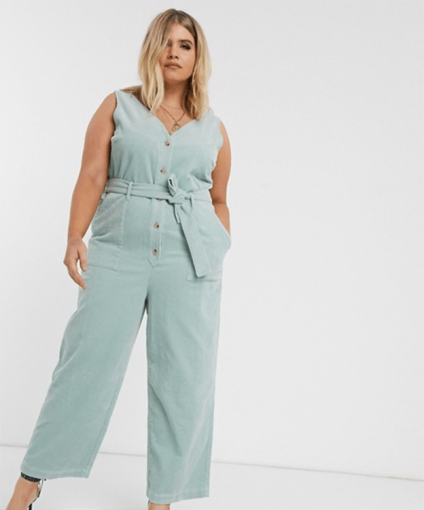 A plus-size model wearing a light blue corduroy jumpsuit.