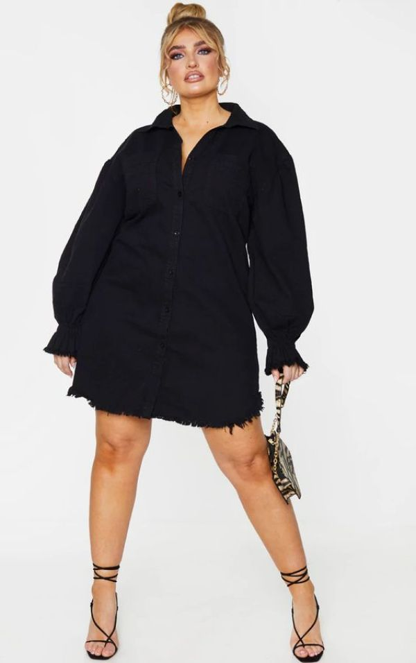 A plus-size model wearing a black denim shirtdress.