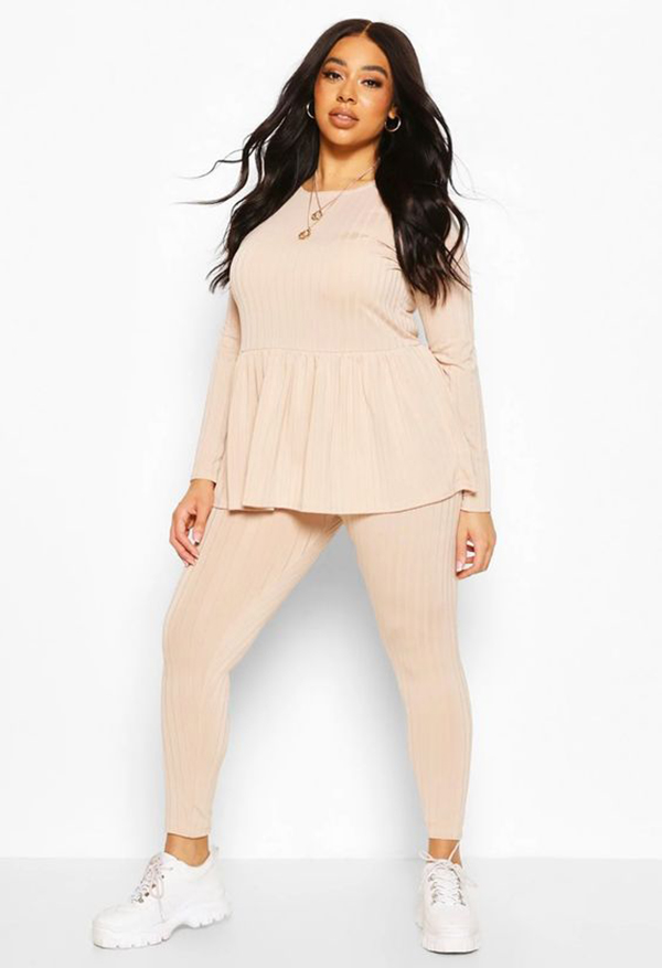 A plus-size model wearing a beige lounge set.